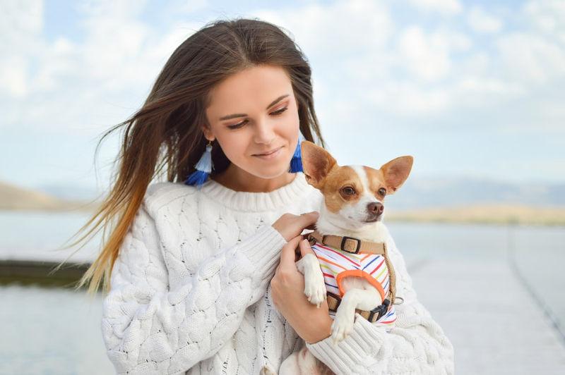Όμορφη γυναίκα με σκυλάκι αγκαλιά