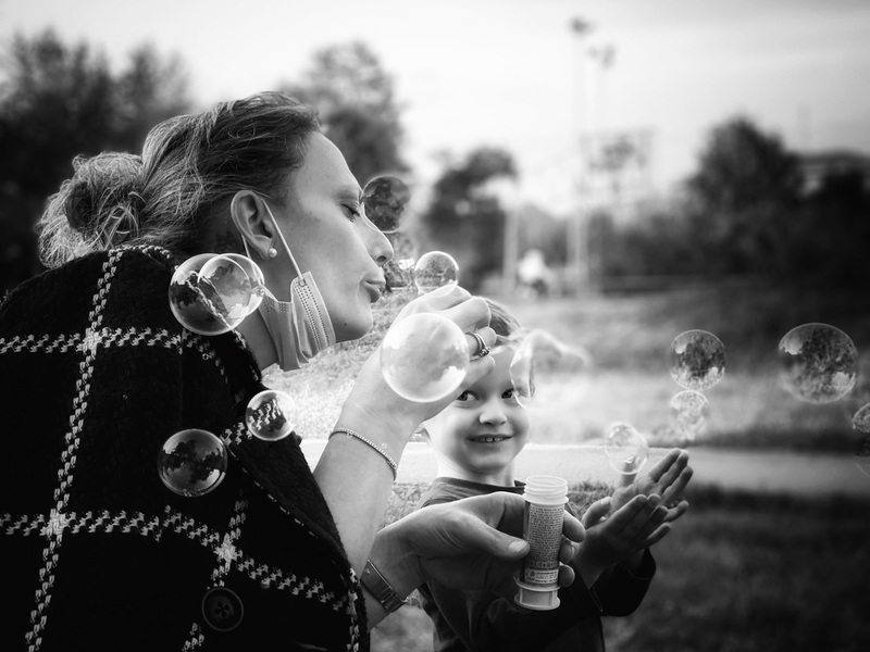travel photographer 2020: μια γυναίκα φυσούσε φυσαλίδες για να διασκεδάσει τον νεαρό γιο της